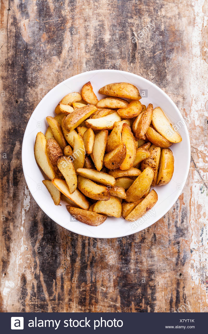 Fried potato 'country-style' chips on plate - Stock Image