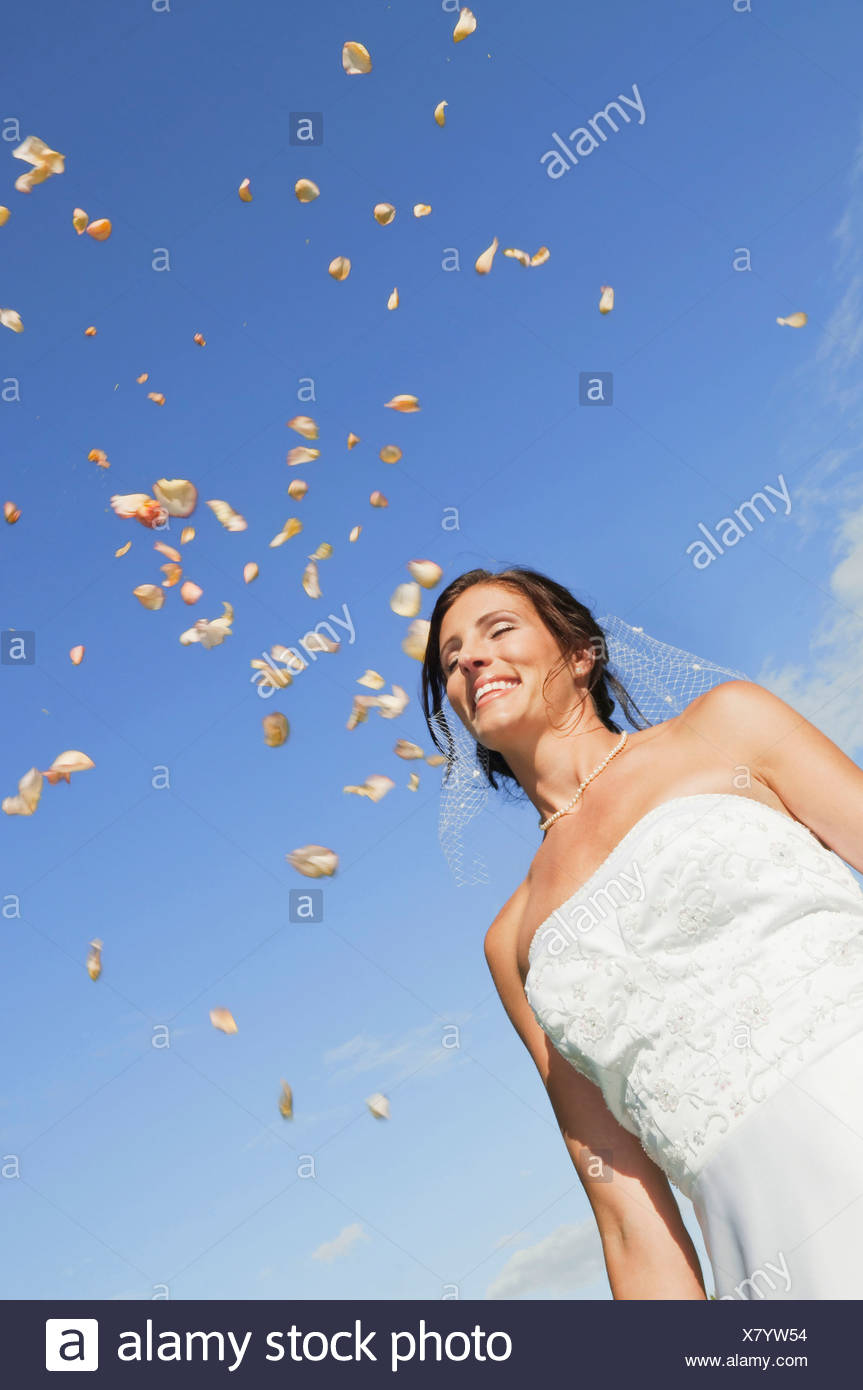 Germany, Bavaria, Bride smiling under falling petals, portrait, low angle view - Stock Image