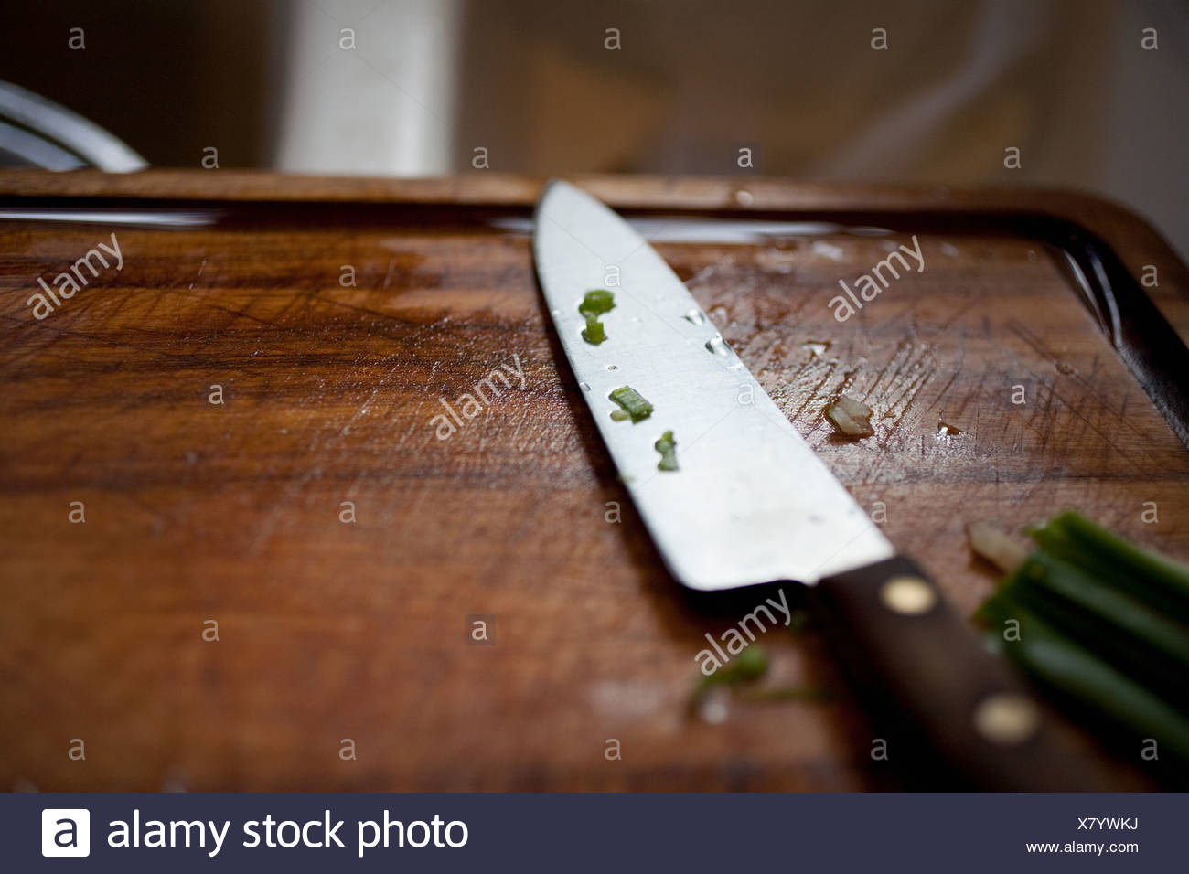 Kitchen knife on wooden chopping board - Stock Image
