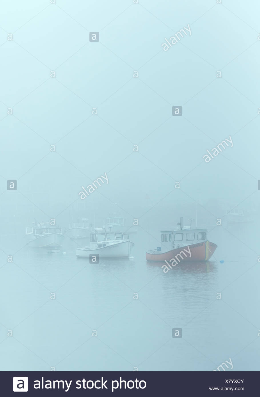 Harbor fishing boats shrouded in heavy fog, Kennebunk, Maine, USA. - Stock Image