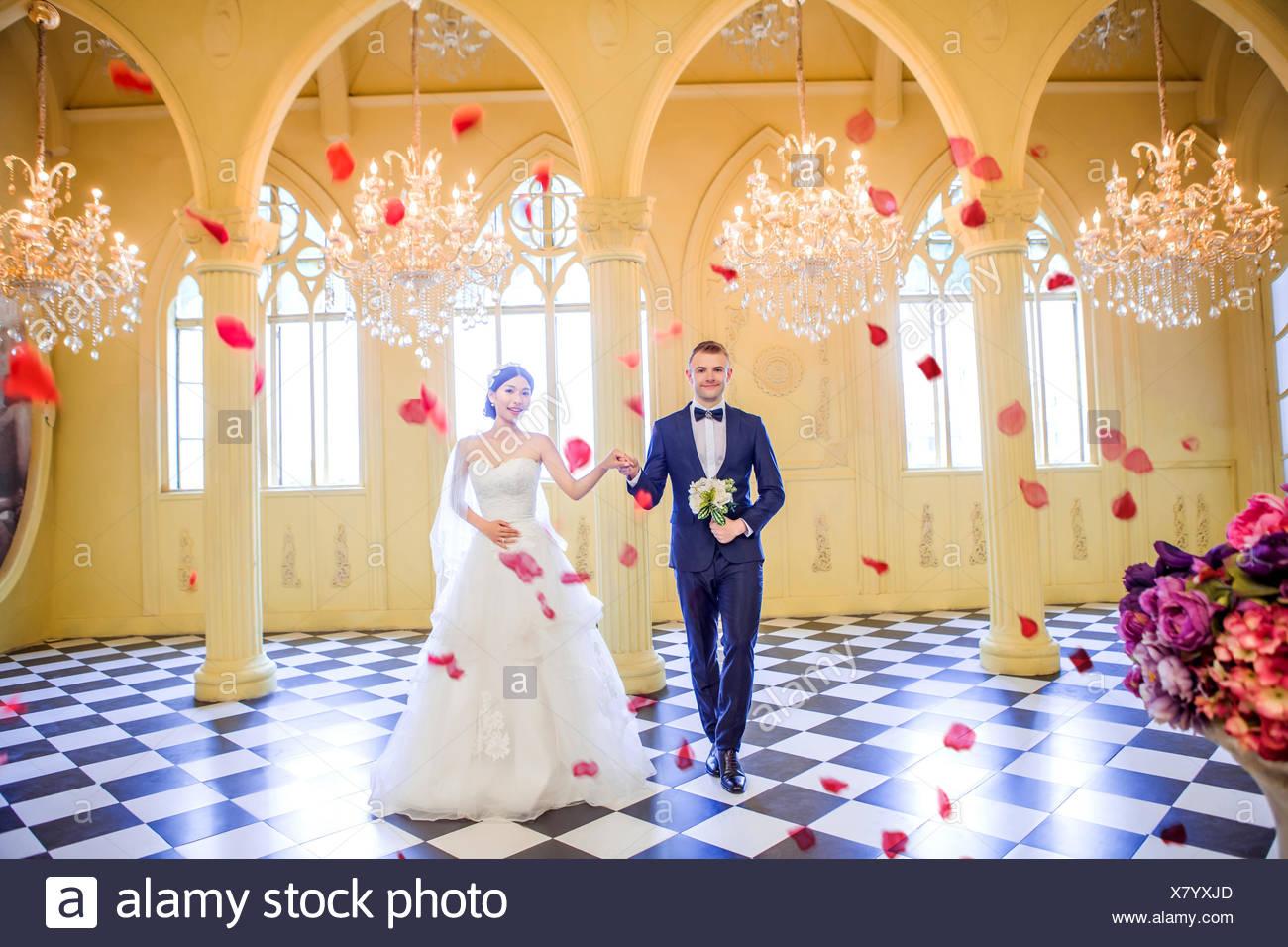 Full Length Of Elegant Wedding Couple Holding Hands In