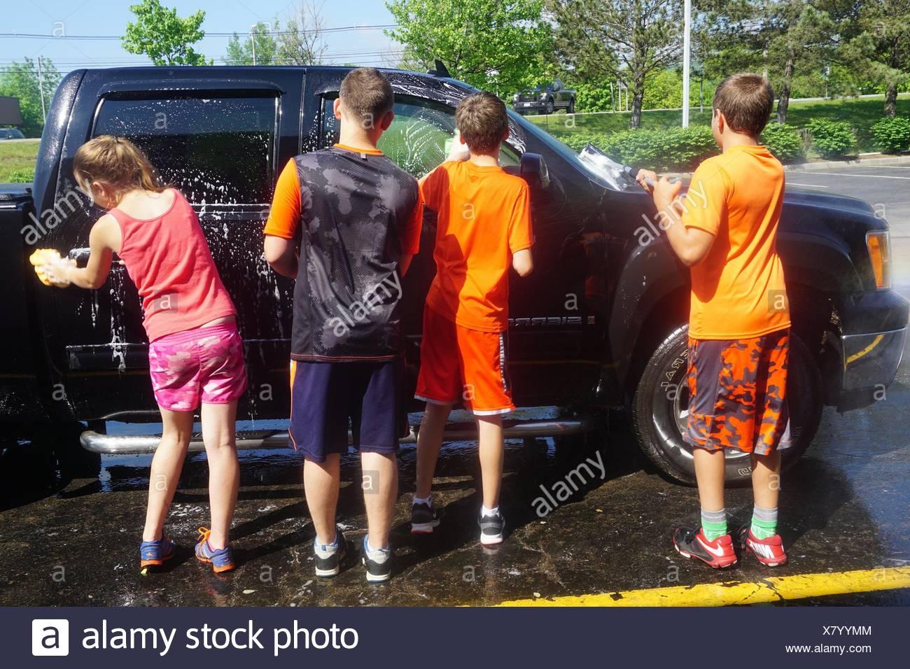 Preteen Boys and Girl Washing Car, Wellsville, New York, USA. - Stock Image