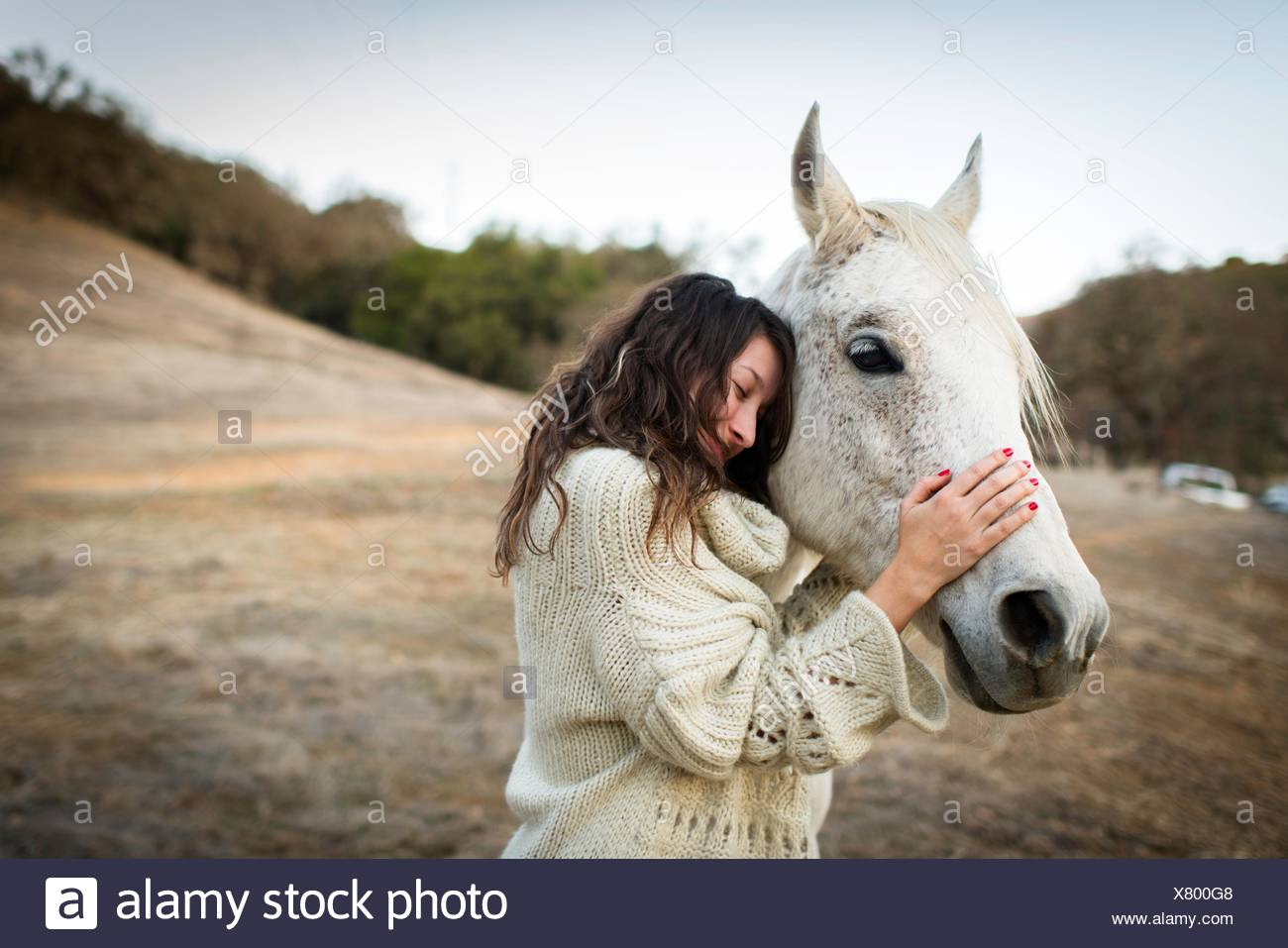 Young woman leaning against and petting white horse in field - Stock Image