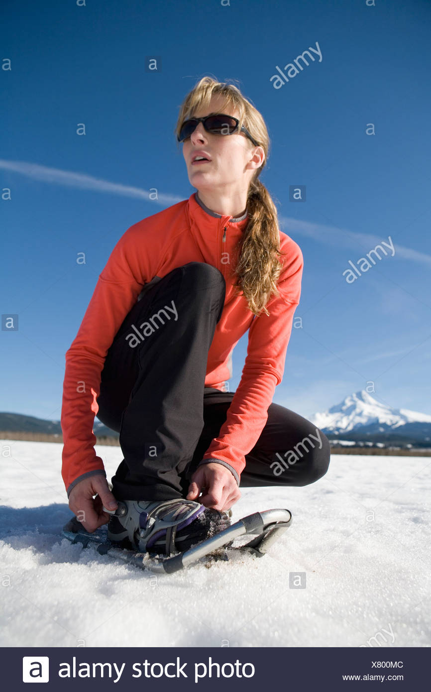Young woman straps on snowshoes with Mt. Hood, Oregon in background. Stock Photo