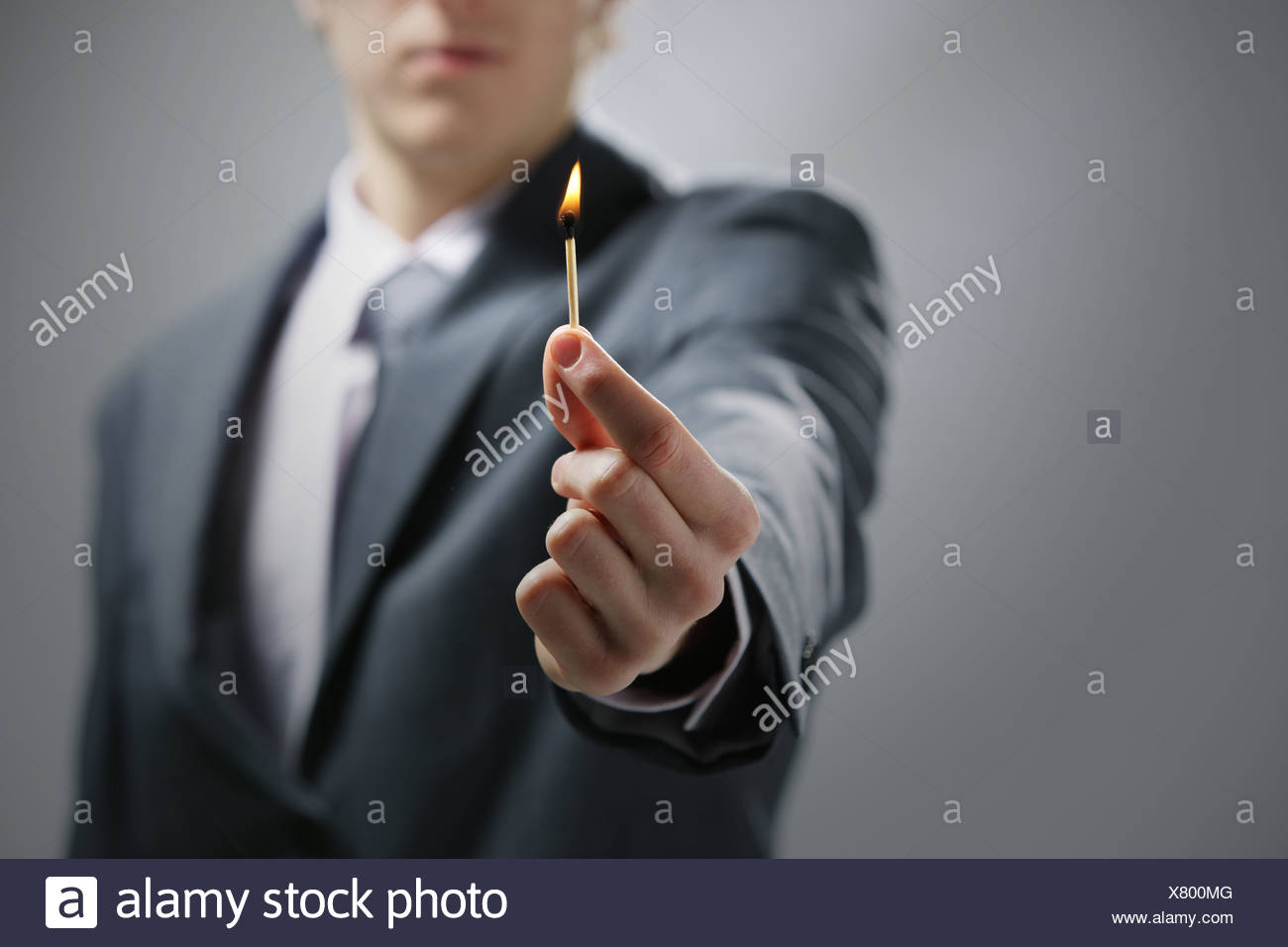 Business man hand holding a burning match - Stock Image