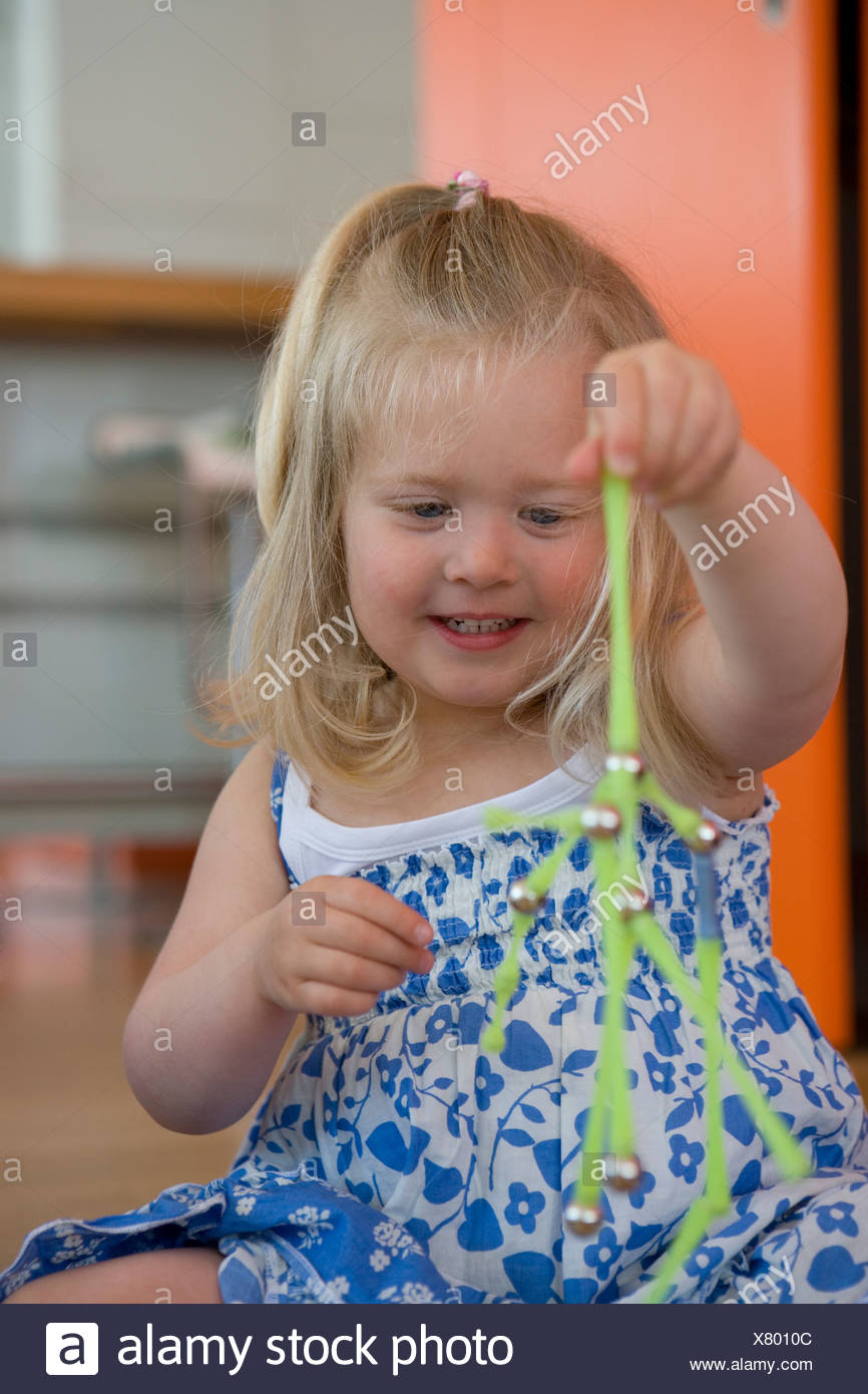 Girl 2-4 playing with toy, smiling, close-up - Stock Image
