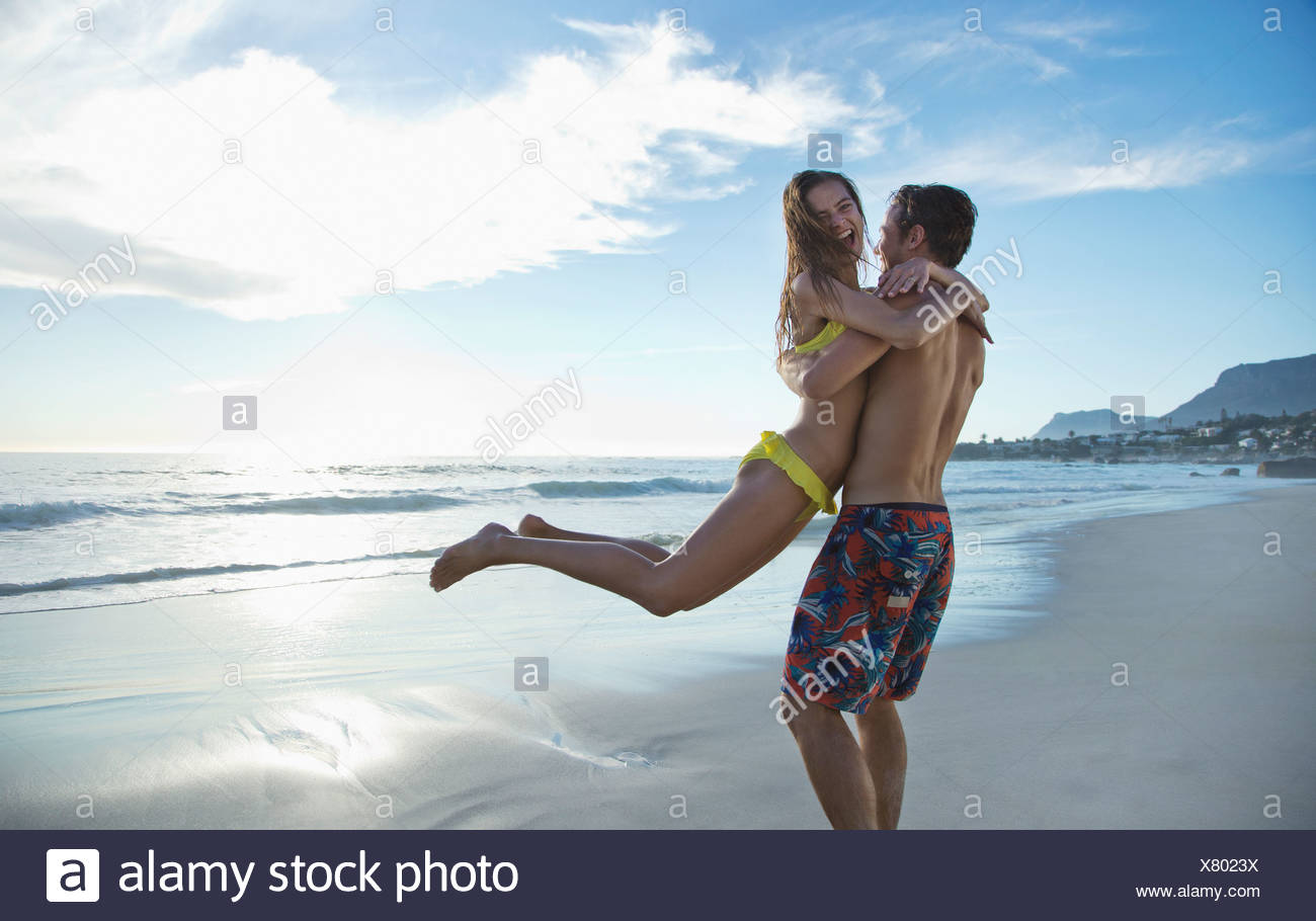 Happy couple hugging and spinning on beach - Stock Image