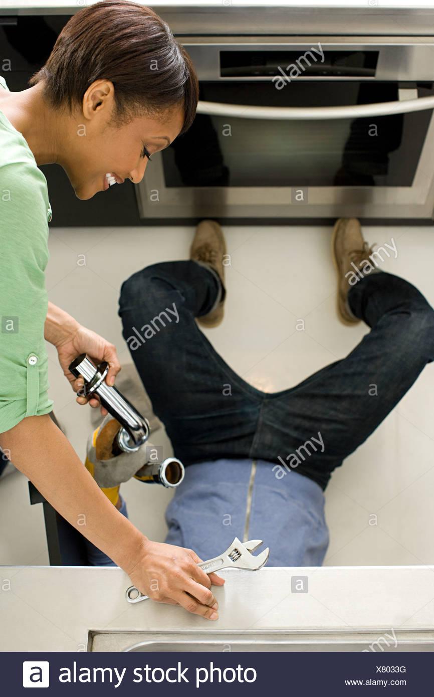 Couple doing plumbing in kitchen - Stock Image