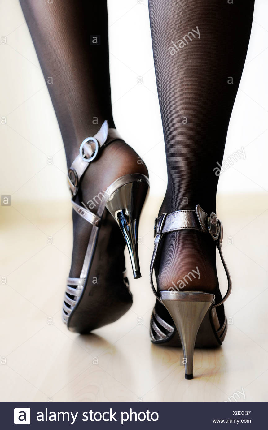 ed385442fb8f Woman s legs wearing black stockings and silver high heels Stock ...