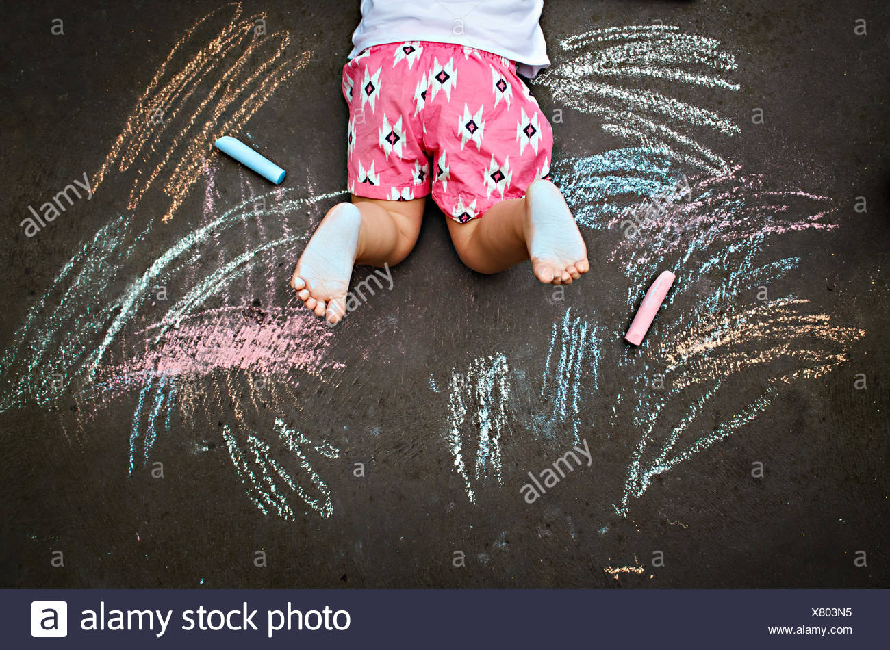 Overhead view of girl lying on ground drawing with chalk - Stock Image