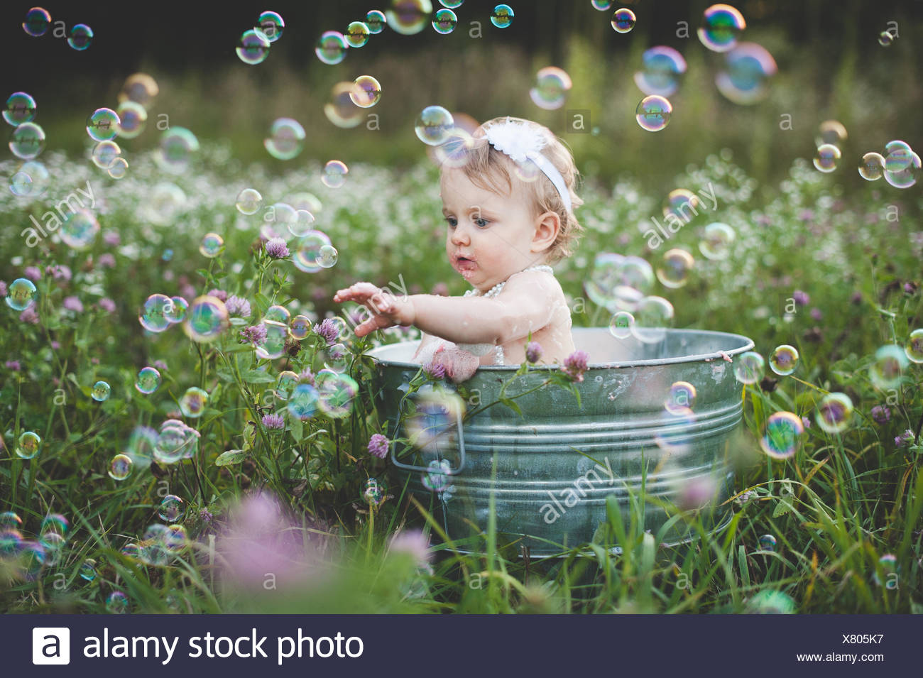 Baby girl in tin bathtub in meadow reaching for floating bubbles Stock Photo