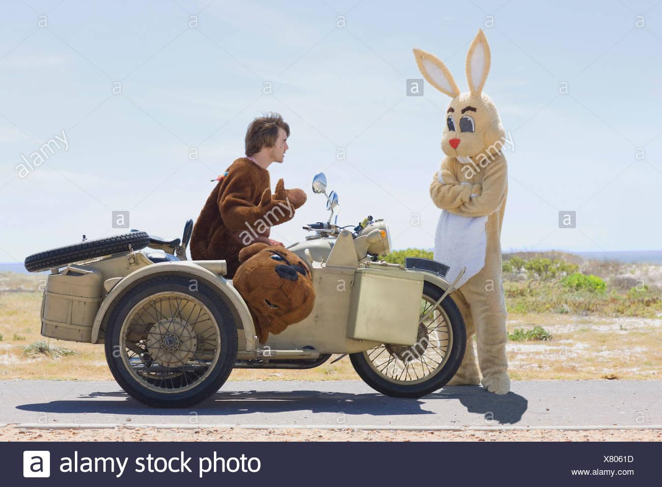 Disguised couple on motorbike - Stock Image