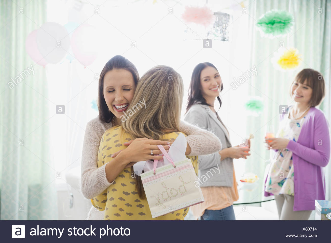 Women embracing at baby shower Stock Photo
