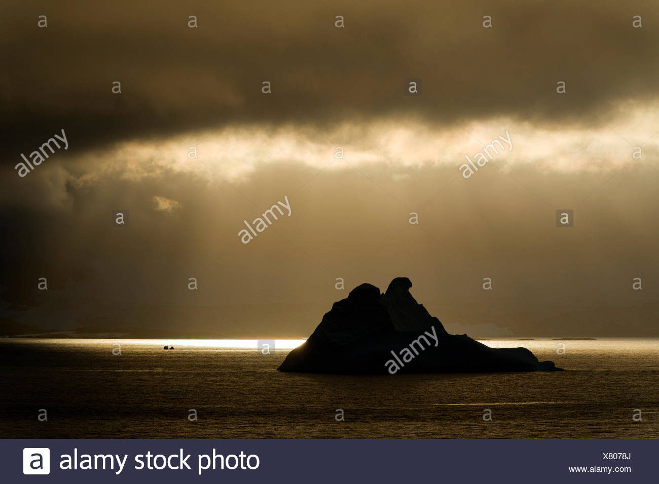 Sunlight shining through a hole in the clouds, silhouette of an iceberg at the front, Errera Channel, Arctowski Peninsula Stock Photo