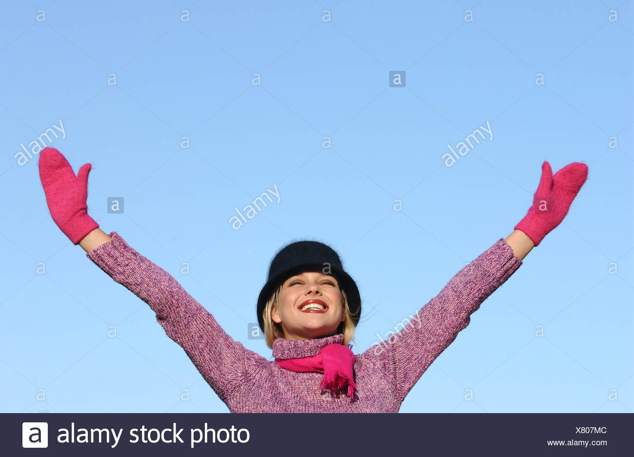 Female blonde hair brown tones of make up wearing black angora hat purple roll neck jumper bright pink scarf and mittens arms - Stock Image