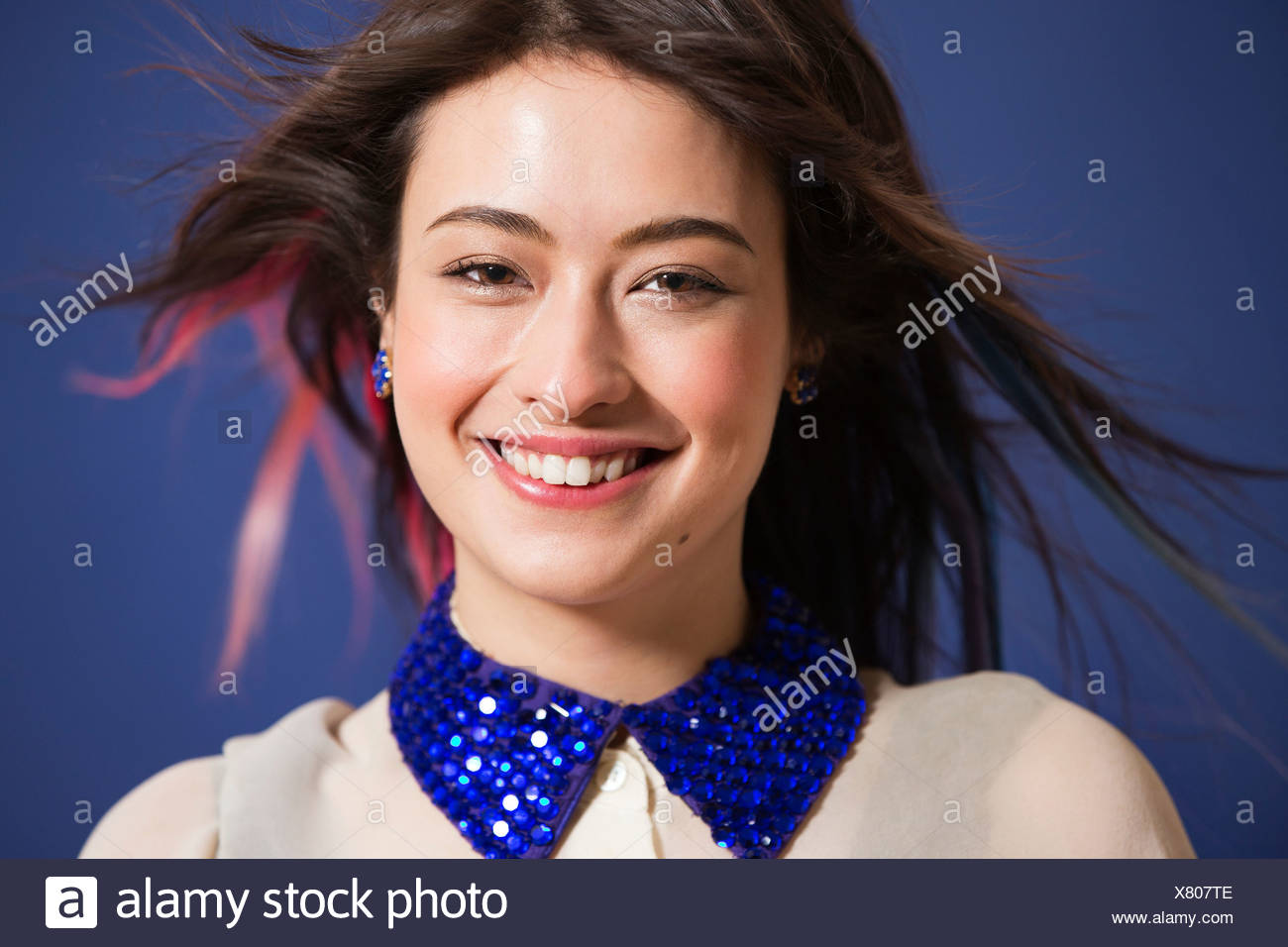 Portrait of young woman with dyed hair and blue sequin collar - Stock Image
