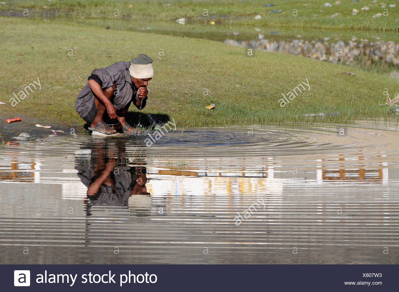 Indian migrant worker for roadworks washes in the morning on the outskirts of the oasis Hundar, Nubra valley, Ladakh, India, Hi - Stock Image