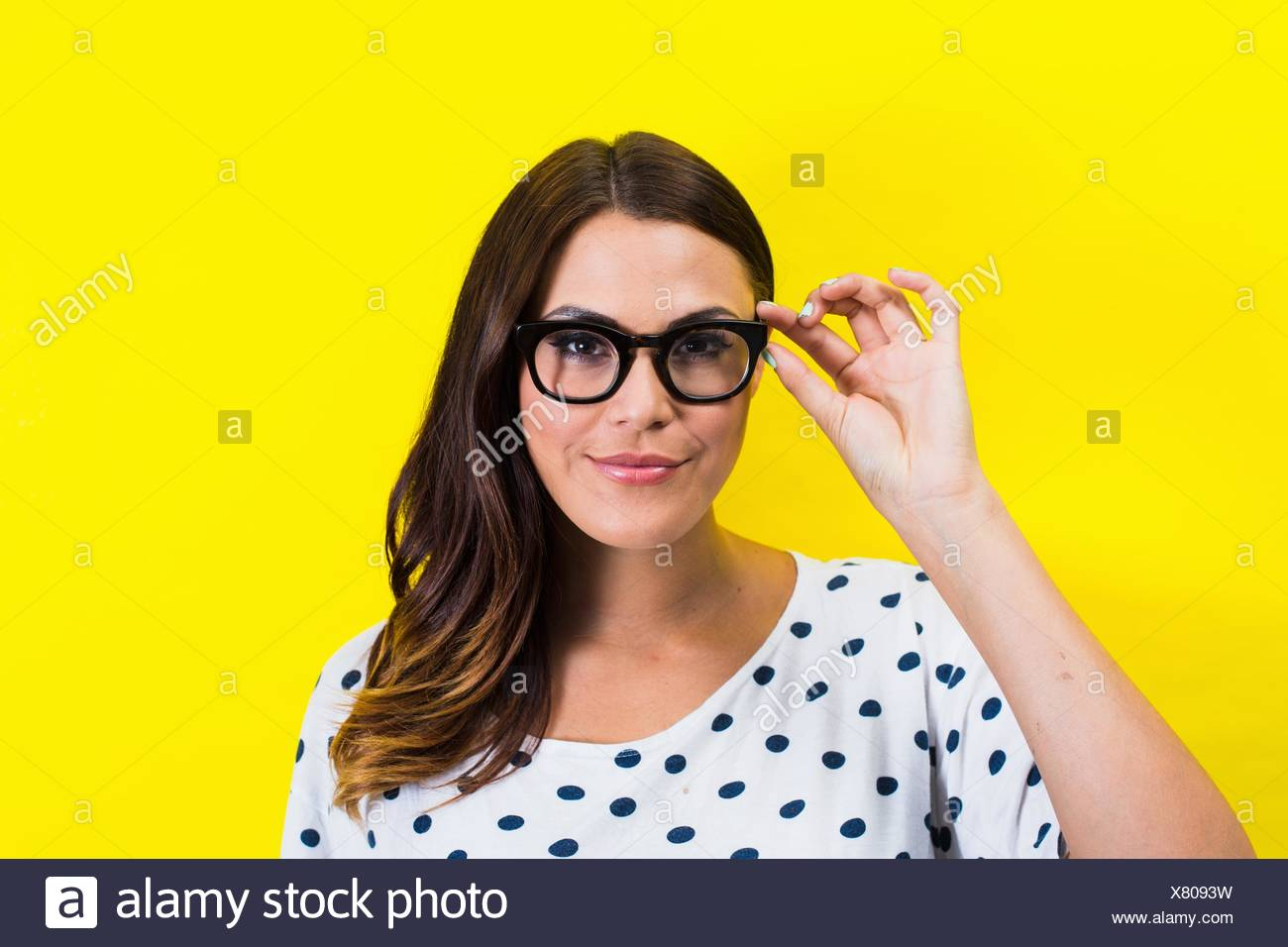 Portrait of young woman holding eyeglasses - Stock Image