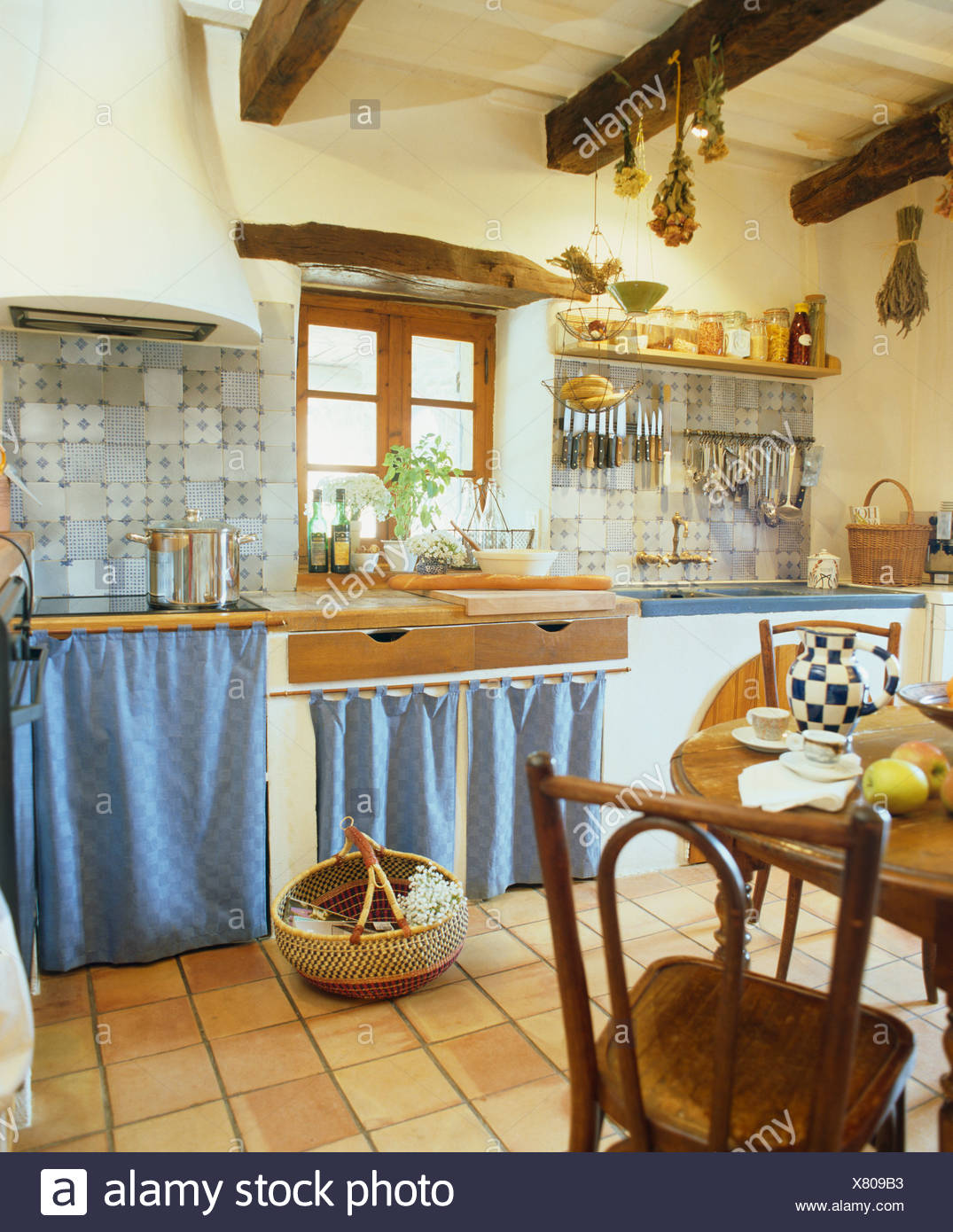 Blue Curtains On Cupboards In French Country Kitchen With Terracotta Tiled Floor And Simple Wooden Chairs And Table Stock Photo Alamy