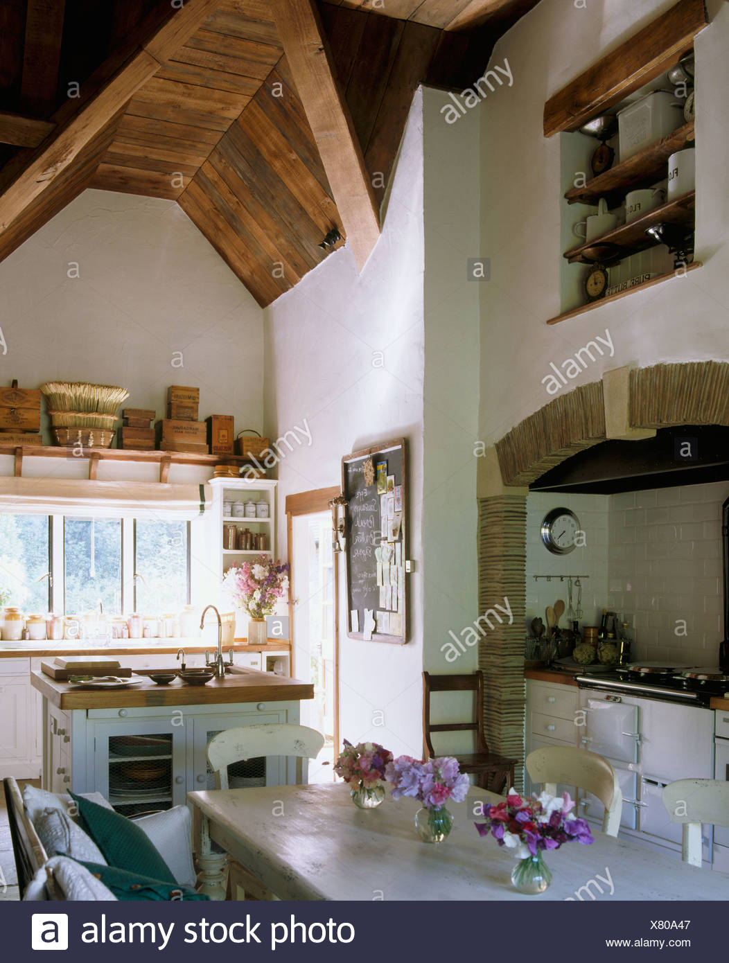 Vases of sweet peas on painted table dining area of large country kitchen with high, vaulted wooden ceiling - Stock Image