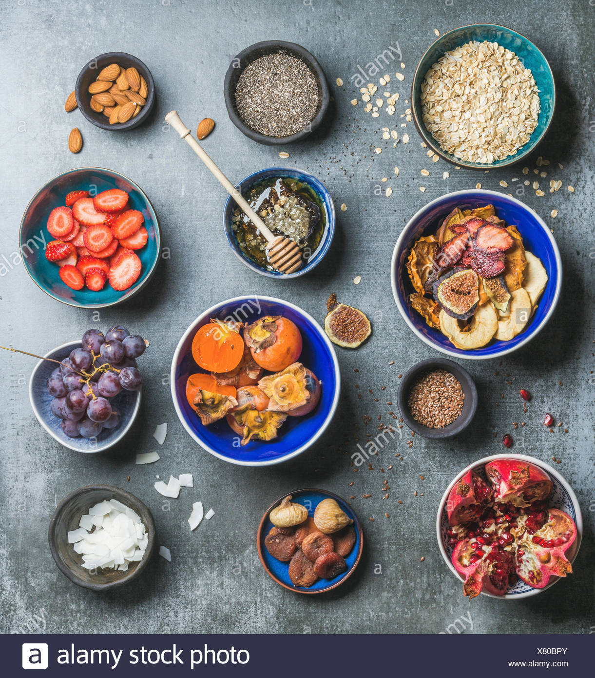 Ingredients for healthy breakfast over grey stone background, top view, square crop. Fresh and dried fruit, chia seeds, oatmeal, nuts, honey. Clean ea - Stock Image