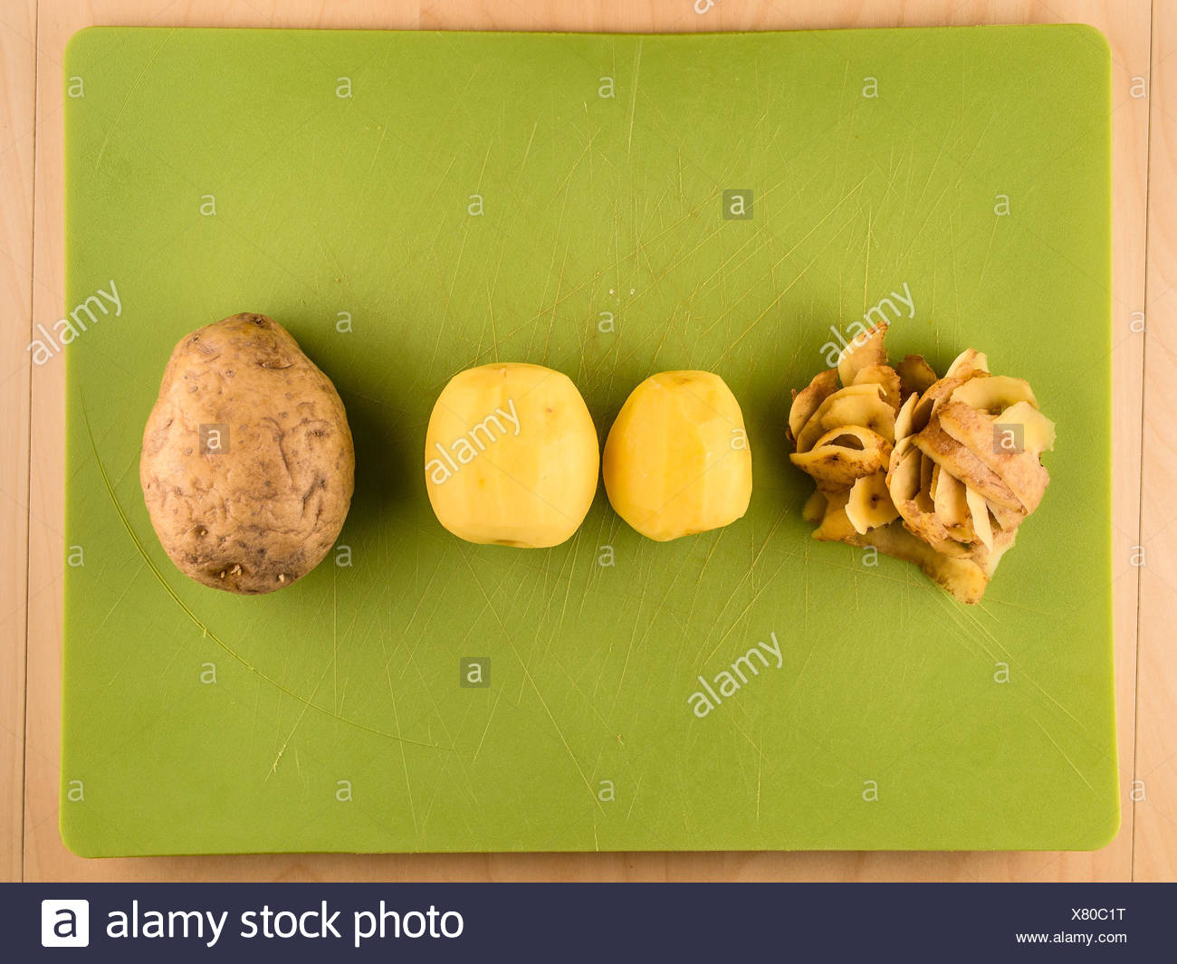 Potatoes, skins in center of green plastic board Stock Photo