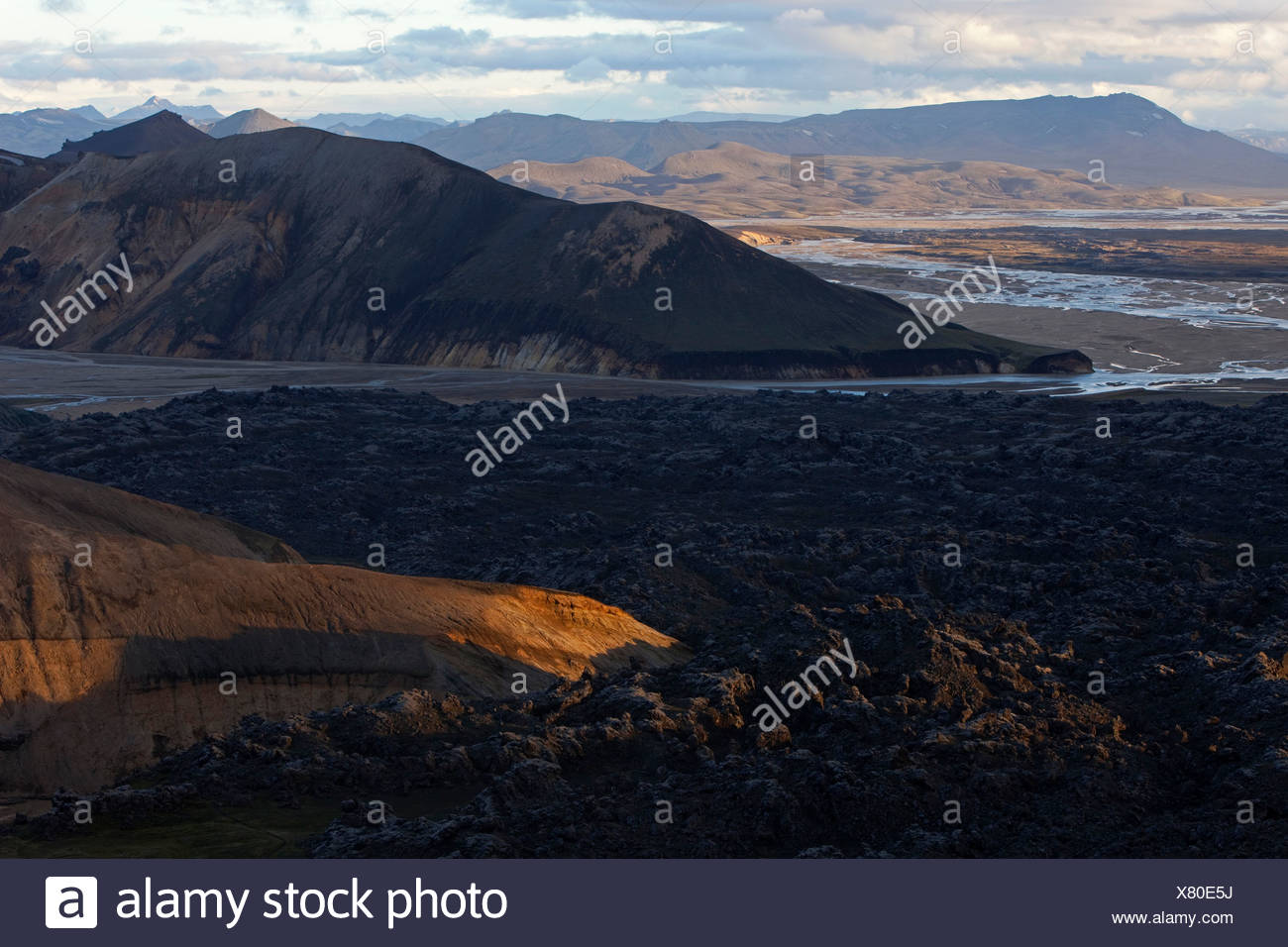 View of peaceful lava field against mountains and clouds in Landmannalaugar, Iceland - Stock Image