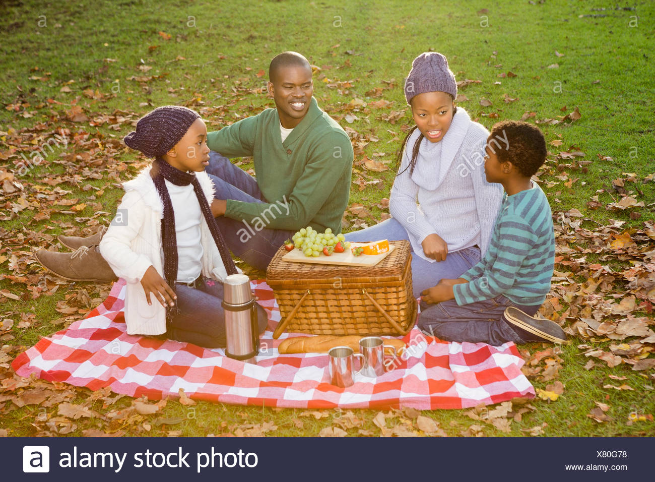 Happy family picnicking in the park together - Stock Image