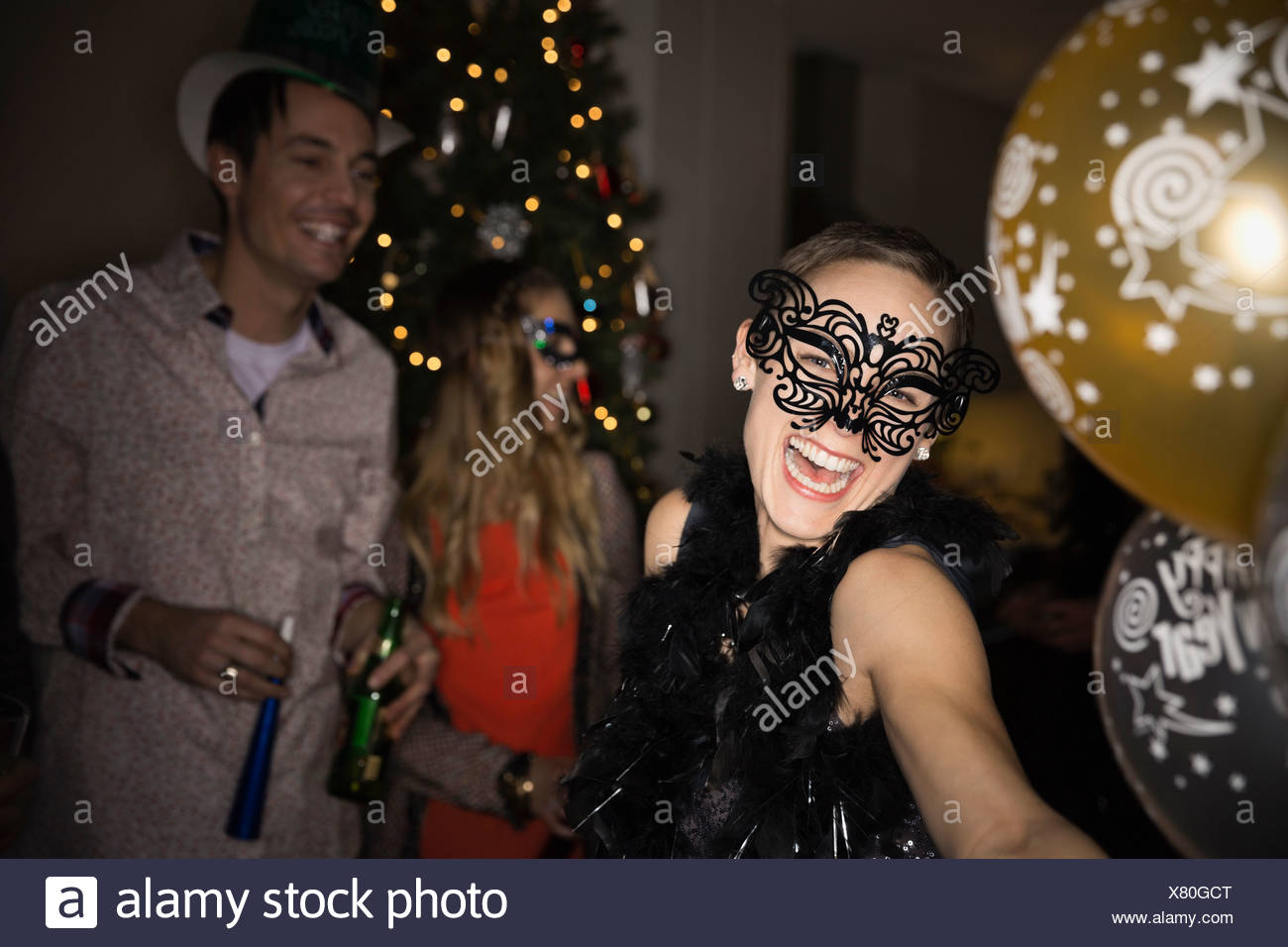Woman in masquerade mask enjoying New Years Eve party - Stock Image