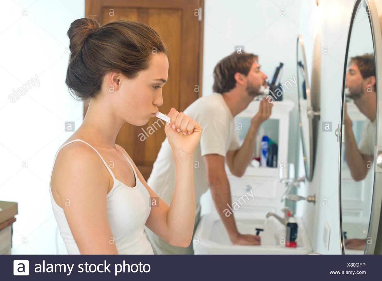 Woman brushing teeth, husband shaving - Stock Image