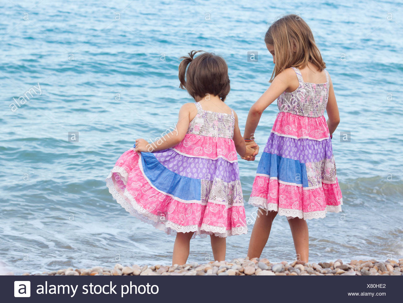 Two sisters standing on beach holding hands - Stock Image