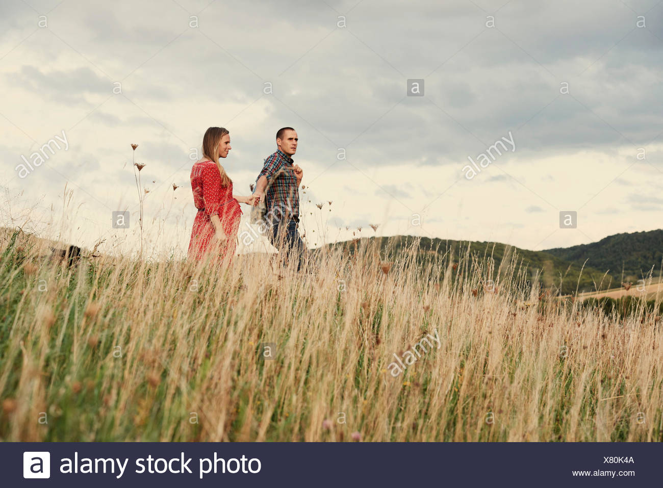 Pregnant mid adult couple holding hands while strolling down hillside - Stock Image