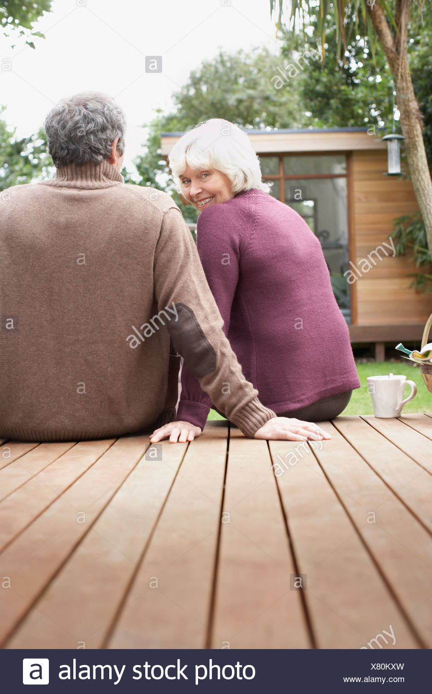 Senior couple sitting on deck in backyard - Stock Image