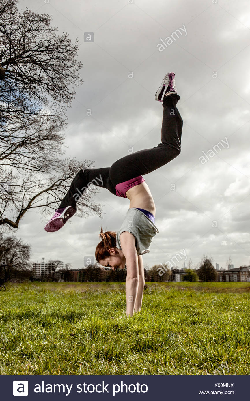 Woman doing handstand with legs apart - Stock Image
