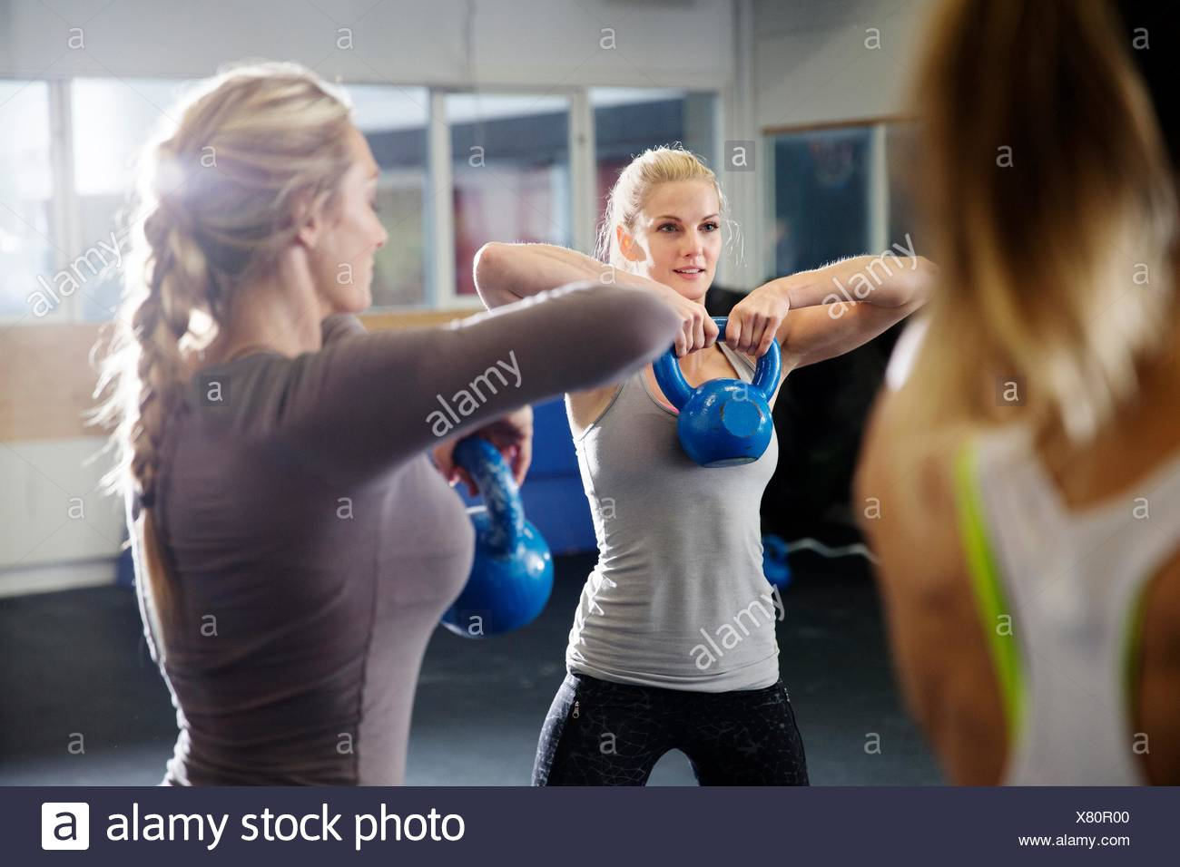 Women training with kettlebells in gym - Stock Image