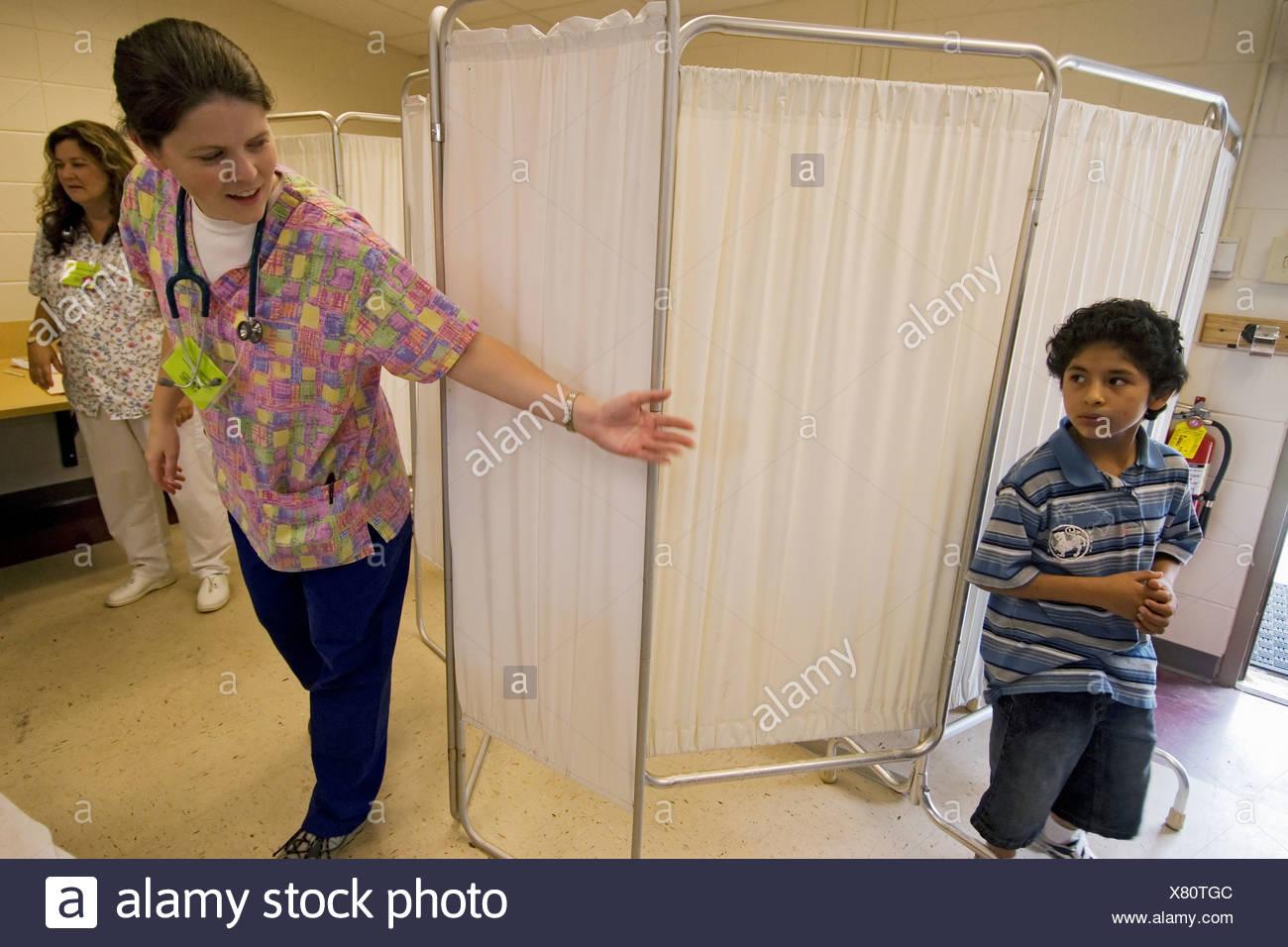 Nursing students faculty Emory University School Nursing in Atlanta Georgia volunteering give checkups in school in camps - Stock Image