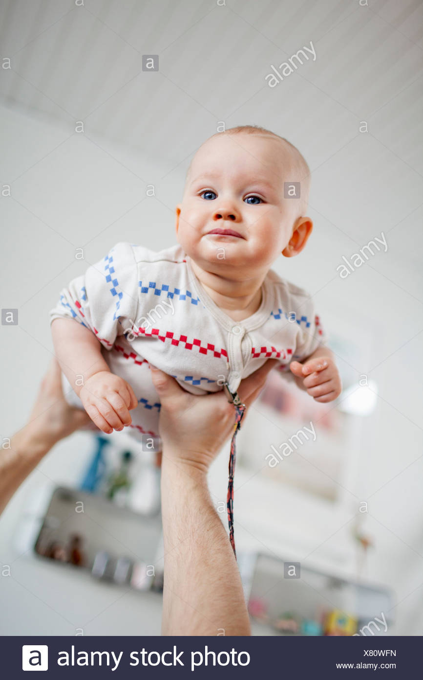 Sweden, Man holding baby son (2-5 months) in hands - Stock Image