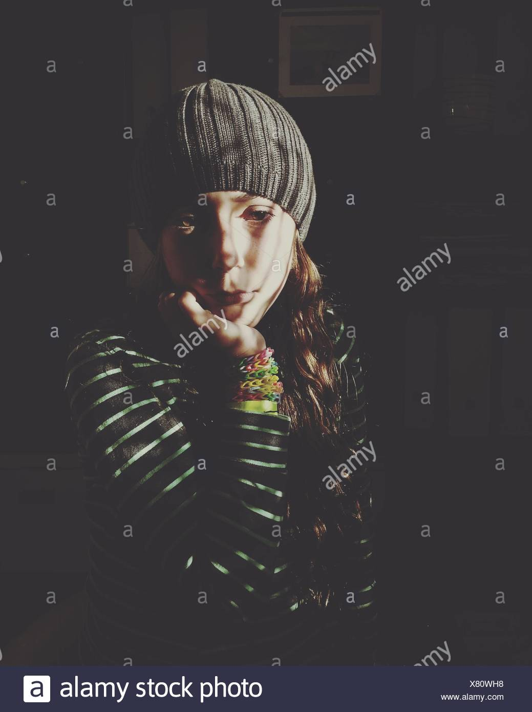 Portrait of girl sitting in shadows - Stock Image