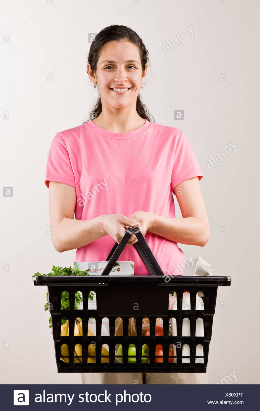 Woman carrying basket of groceries - Stock Image