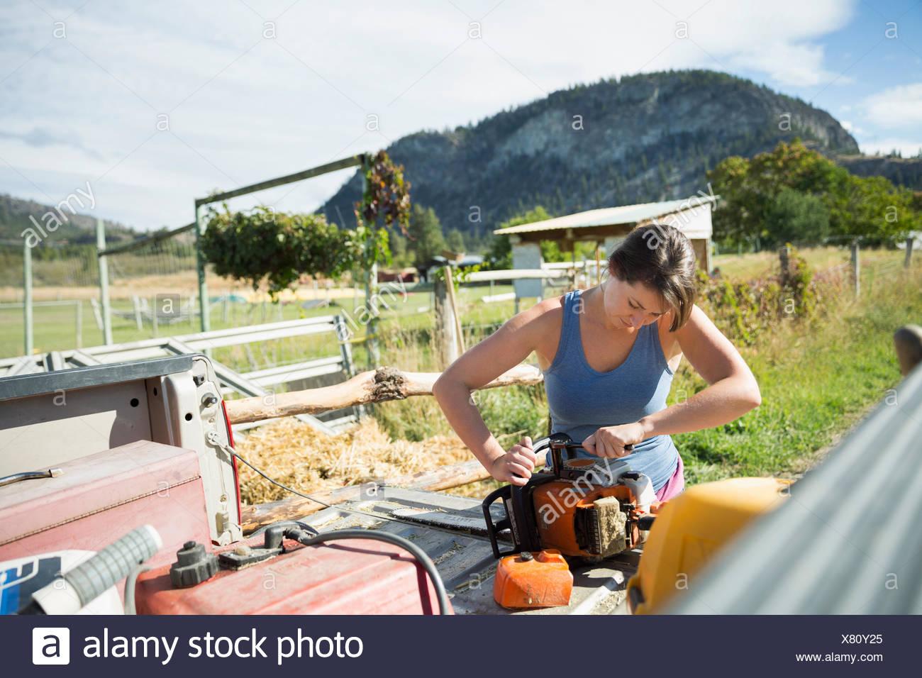 Female farmer fixing equipment on truck bed on sunny farm - Stock Image