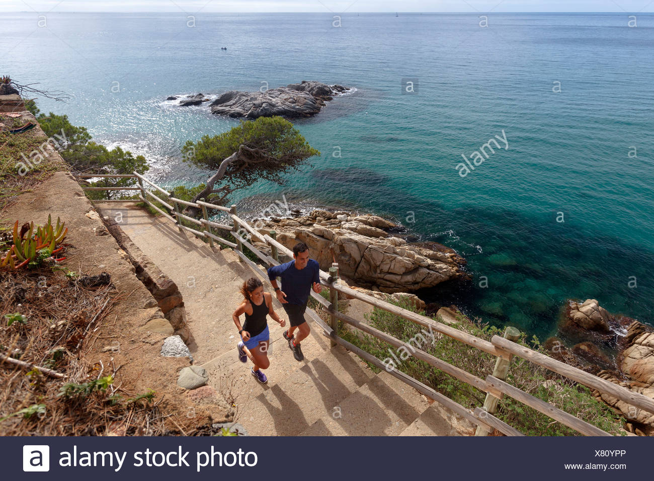 Couple running on paved steps - Stock Image