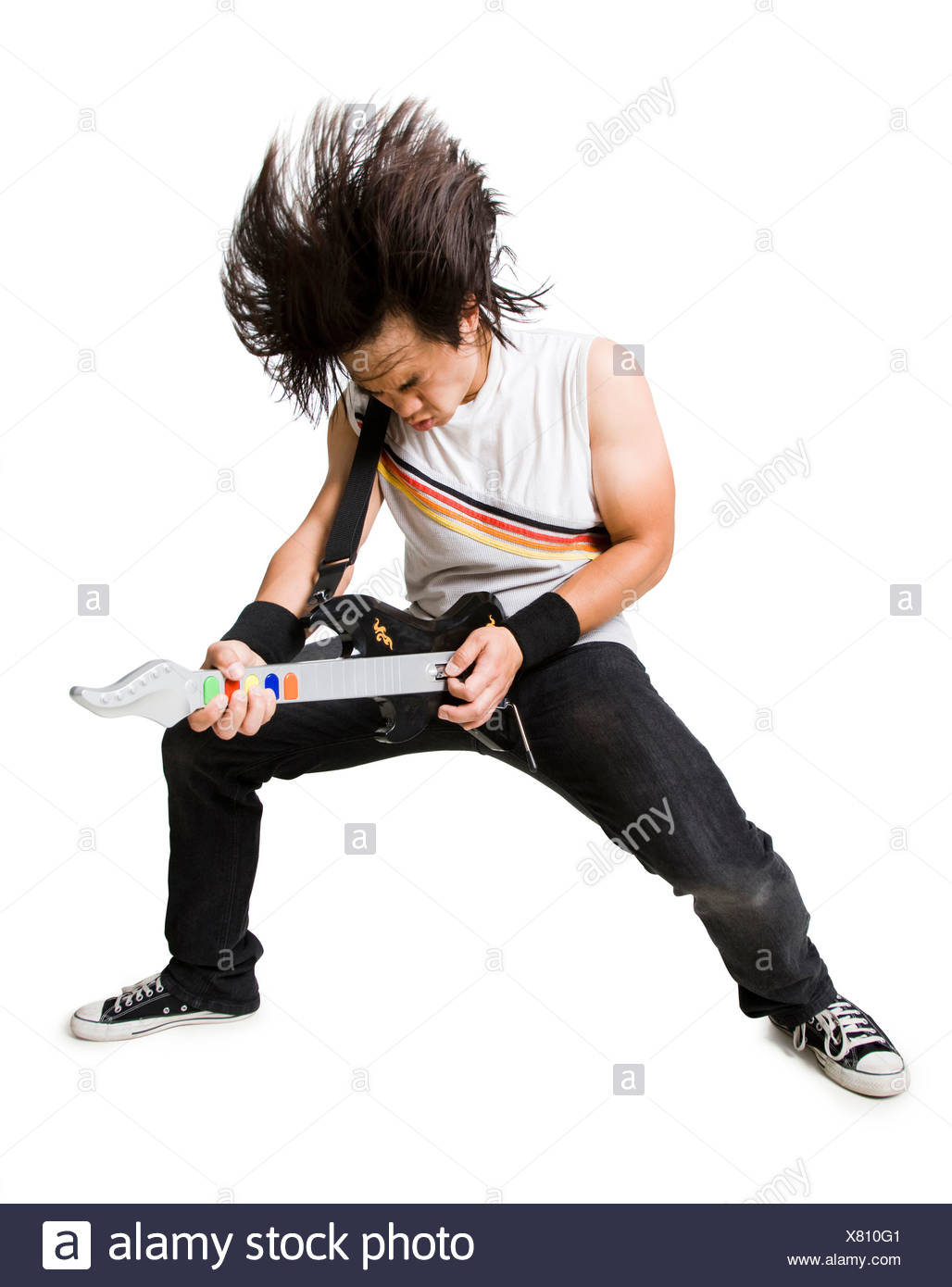 Young man playing guitar video game, portrait - Stock Image