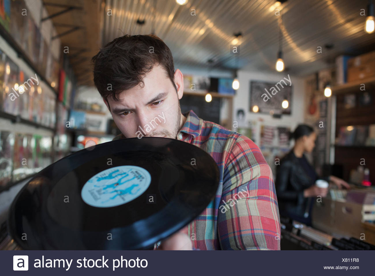 Young man and woman in a record store. - Stock Image