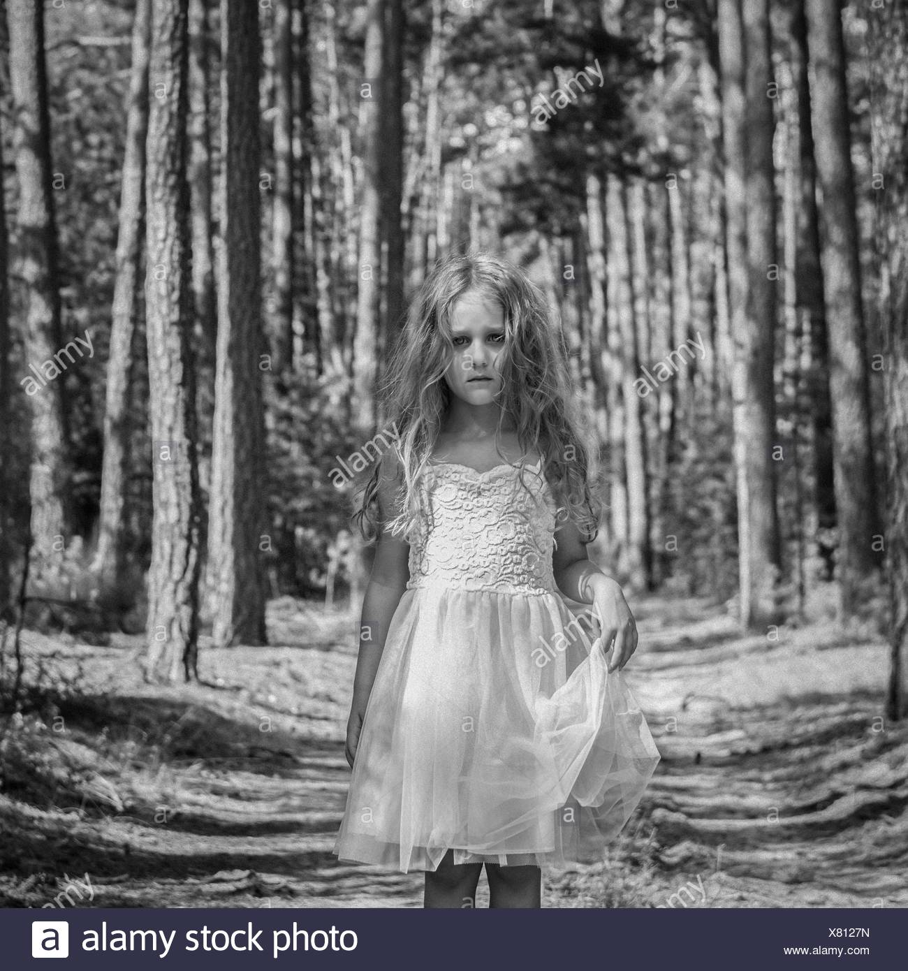 Portrait of sad girl (4-5) in forest - Stock Image