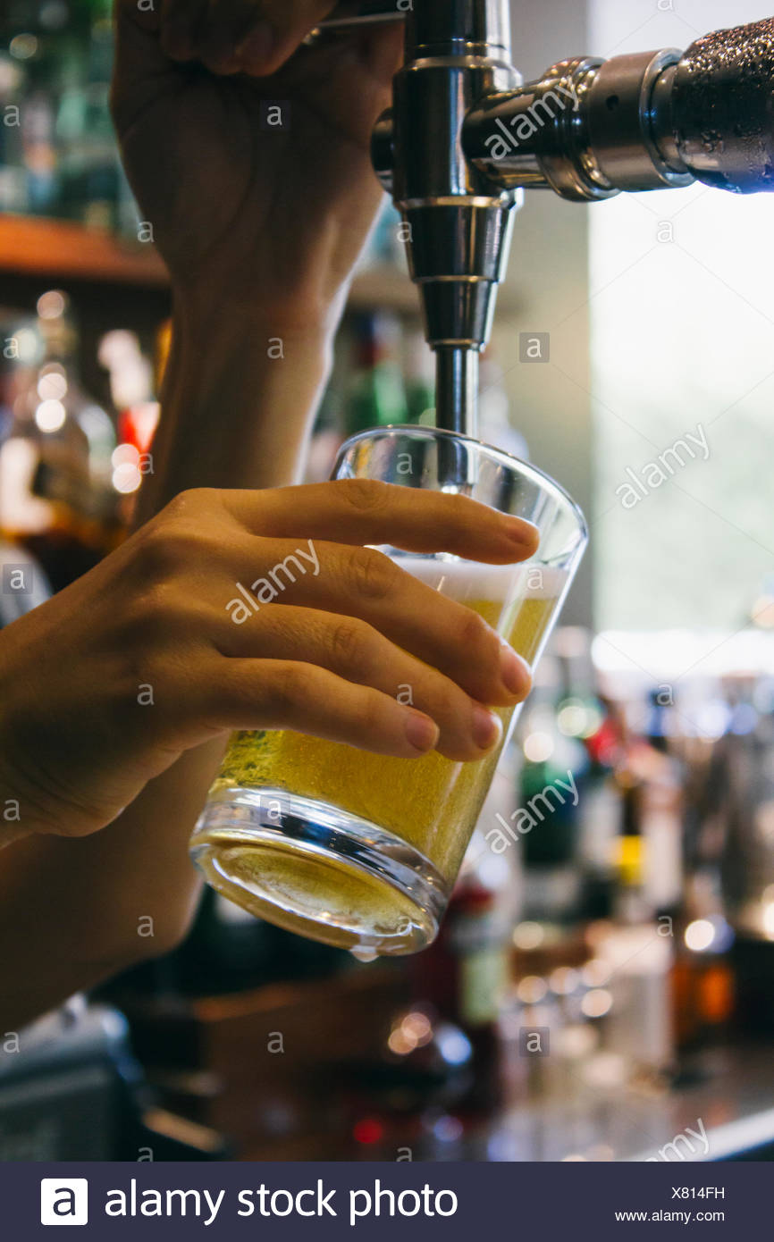 Waitress tapping fresh beer - Stock Image