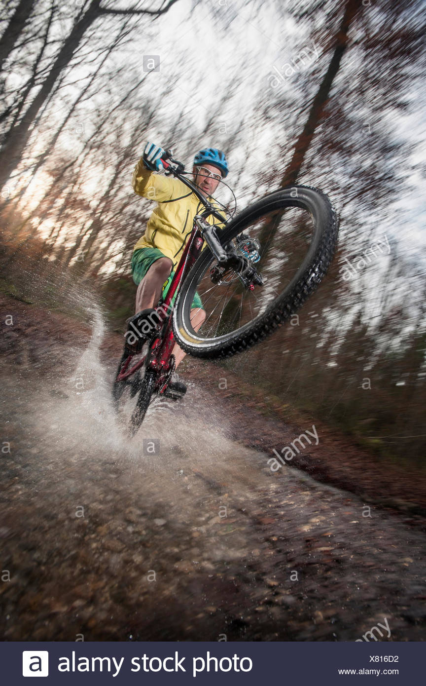 Mountain Biker rides on the rear wheel through a stream in the forest, Bavaria, Germany Stock Photo
