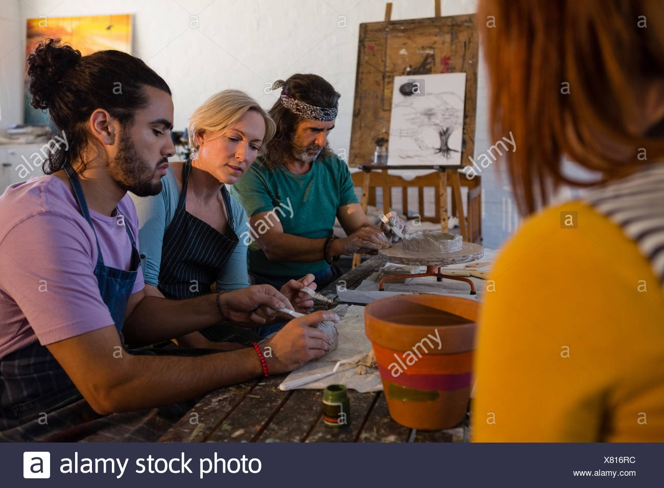 Teacher guiding students making clay products in art class - Stock Image