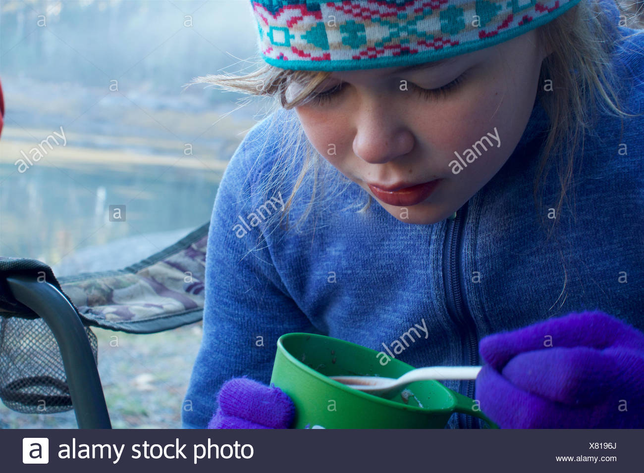 Camper enjoying her hot chocolate on a chilly fall morning in Acadia. - Stock Image