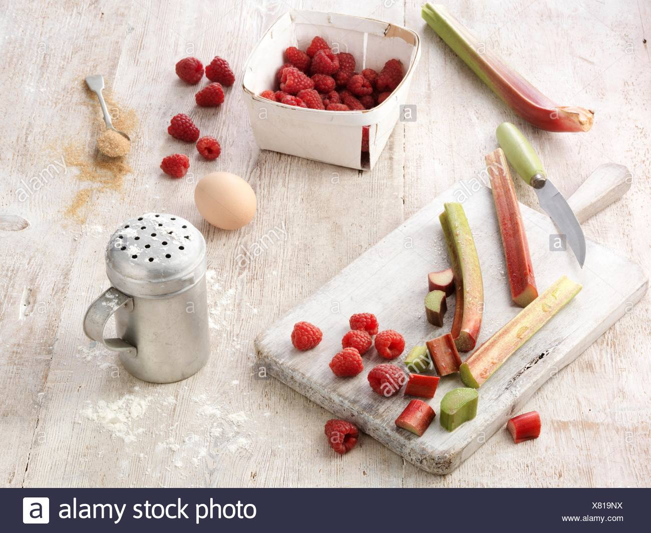 Ingredients for rhubarb and raspberry cobbler pudding on whitewashed wooden table - Stock Image
