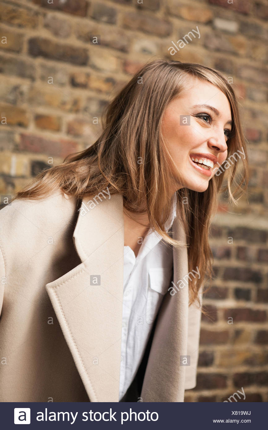 Woman with wide smile, brick wall in background Stock Photo